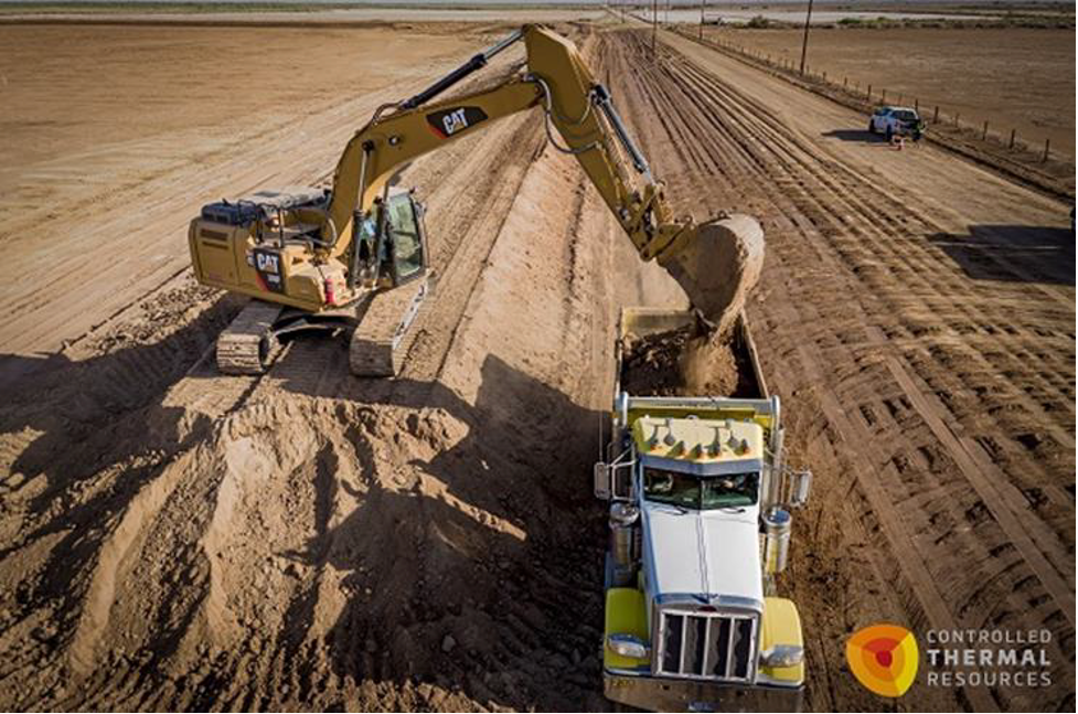 Yellow backhoe loading dirt into dump truck as geothermal pipeline is being constructed