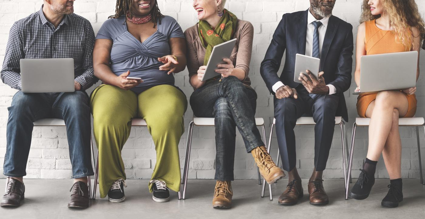 Stock photo of a diverse group of people sharing information on their devices.
