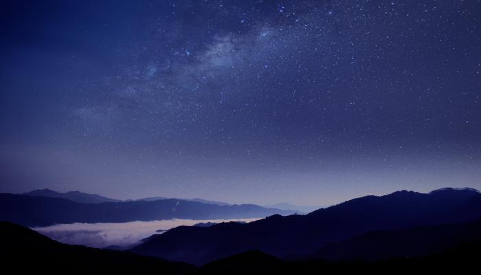 Silhouette of mountains against blue night sky with stars