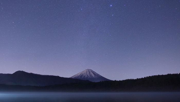 A lake at nighttime with a starry sky and a mountain in the background.