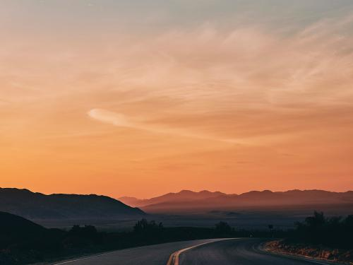 View down empty California road across the desert at sunset